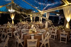 Clear tent with candle centerpiece and twinkle lights.