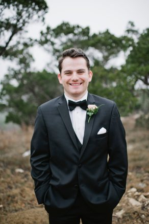Smiling groom in tuxedo with bowtie.