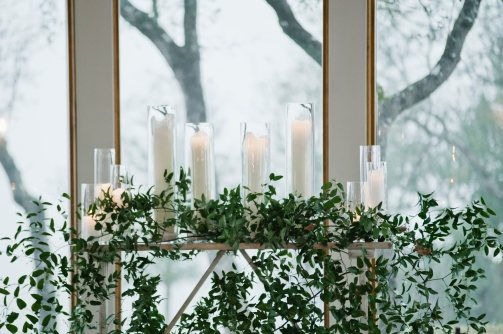 Tall pillar candles with smilax greenery on altar table for ceremony.