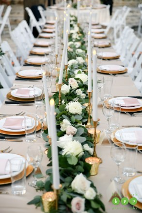 Long dinner table with greenery garland, loose white blooms and LED taper candles.