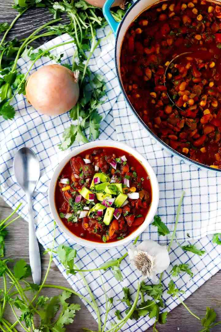 A flatlay photo of vegetarian chili with a dutch oven of chili next to it and cilantro and onions and a towel in the background.