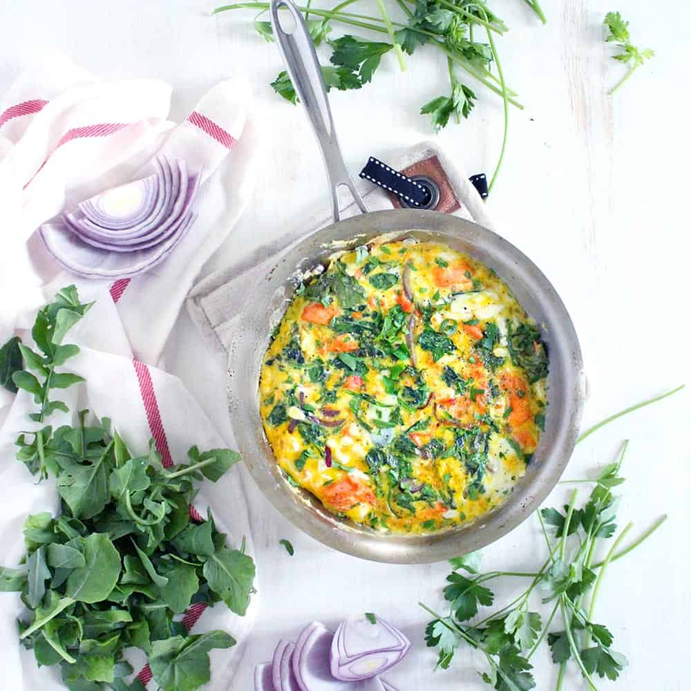 This salmon, arugula, and feta frittata is a great way to use up leftover cooked salmon! This low-carb, gluten free, easy recipe comes together in only 20 minutes.