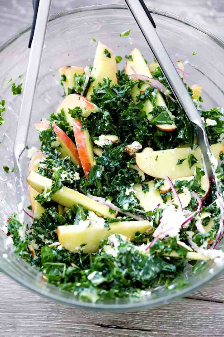 Mixing a kale salad together in a glass bowl with tongs.