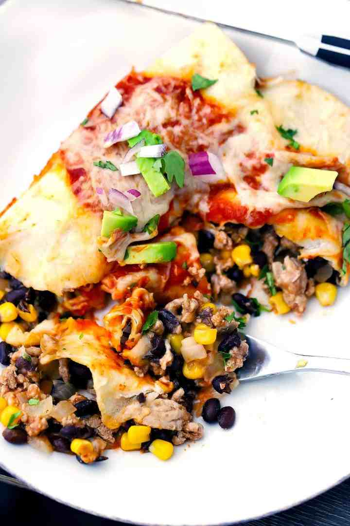 Turkey enchiladas cut in half on a white plate with black beans and corn.