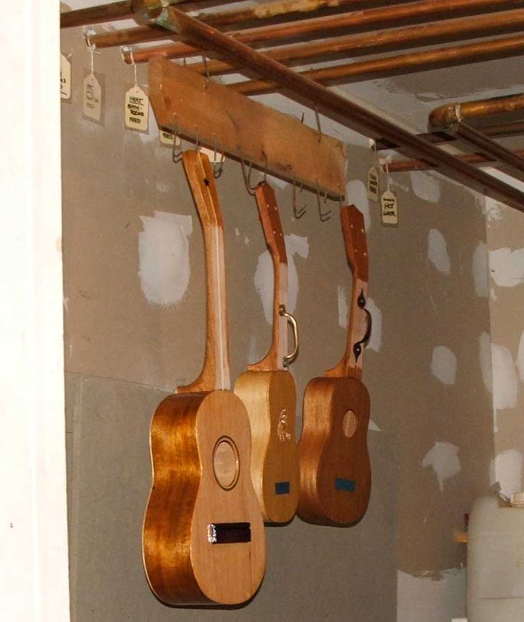 one tenor and two soprano ukuleles in the varnishing room