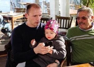 Jürgen Brähmer zeigt seiner Tocher Jasmi Bilder auf seinem Handy. Mananger Peter Hanraths schaut zu
