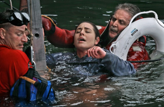 Boston firefighters, from left, John Goggin and Joseph Hughes work to rescue a woman who fell into the frigid waters of Boston Harbor on December 21, 2012.