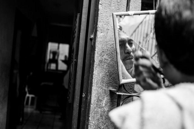 A man shaves in the one mirror in Talita Cumi.