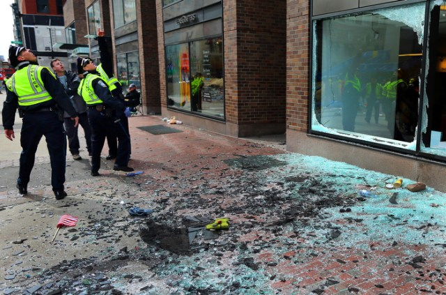 Boston-4/15/13- Boston Police  officers look at blown out windows at the scene of the first terrorist bombing of the Boston Marathon on the sidewalk of Boylston Street.