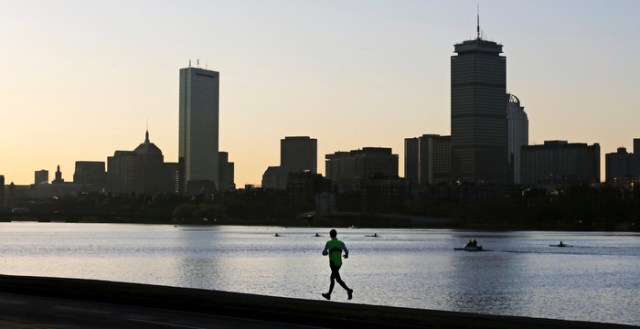 A solitary runner heads down the banks of the Charles River in Cambridge, Mass., in front of the Boston skyline, at dawn the morning after explosions killed three and injured more than 260 at the Boston Marathon, Tuesday, April 16, 2013.