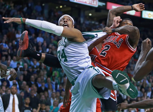 The Bulls Nate Robinson has a good grip on Celtics captain Paul Pierce as he stretches his jersey as they battle under the boards during the final frantic seconds of the game.