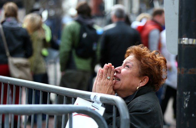 Boston-4/15/13- A woman kneels and prays at the scene of the first explosion on Boylston Street At the finish line of the Boston Marathon.