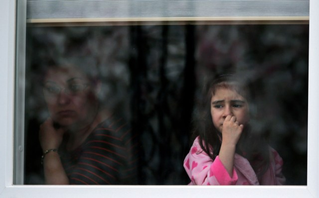 A girl looks out the window of her family's home as a SWAT team drives through her neighborhood while searching for a suspect in the Boston Marathon bombings in Watertown, Mass., Friday, April 19, 2013.