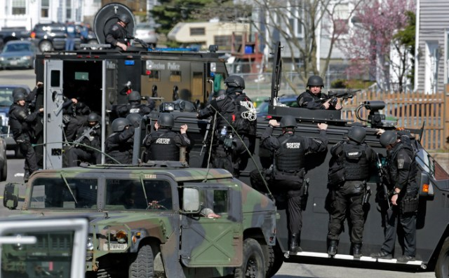 Tactical teams drive through a neighborhood while searching for a suspect in the Boston Marathon bombings in Watertown, Mass., Friday, April 19, 2013.
