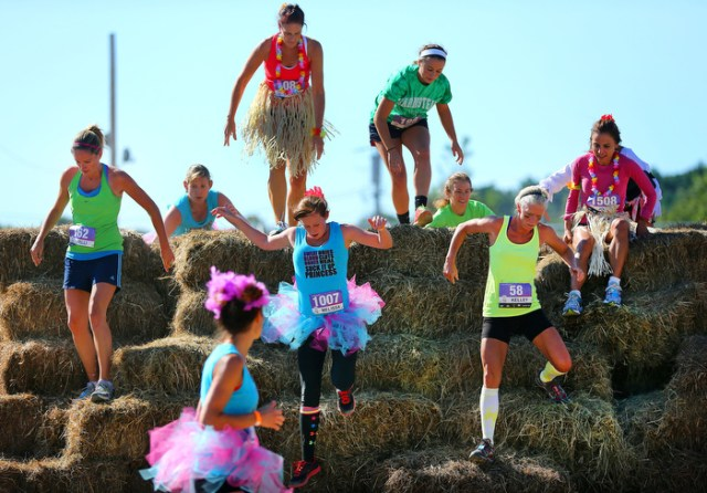 Marshfield-09/07/13 Participants  in the Shape Diva Dash 5k obstacle race at the Marshfield Fairgrounds make their way over a hay bale obstacle along the course.