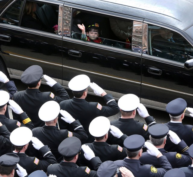 "On the way to the cemetery, a young ""captain"" waves to the crowd.  The funeral for Boston Fire Lt. Edward J. Walsh, Jr. is held in Watertown, on Wednesday, April 2, 2014."