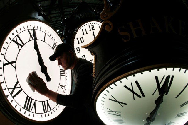 Dave LeMote wipes down a post clock at Electric Time Company, Inc. in Medfield. Most Americans will set their clocks 60 minutes forward before heading to bed Saturday night, but daylight saving time officially starts Sunday at 2 a.m. local time.