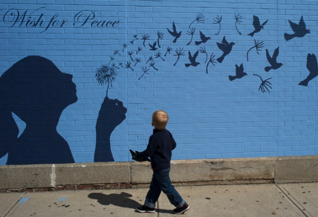 "A boy looks up at a mural reading ""A Wish for Peace"" in Medford, Massachusetts September 15, 2014."