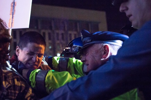 November 25, 2014 – A police officer strangles a man as other protestors attempt to push their way onto the I-93 highway in Boston, Mass.
