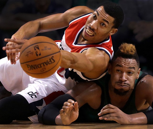 Washington Wizards forward Otto Porter Jr. and Boston Celtics center Jared Sullinger dive to the parquet floor while chasing a loose ball during the third quarter of an NBA game at TD Garden.