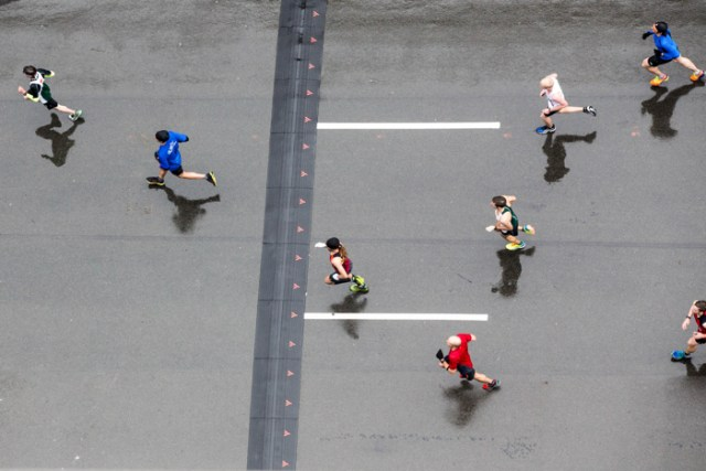 A wet Boylston Street reflects the shadows of the runners as they symmetrically brave past the rain and the cold while approaching the finish line of the 2015 Boston Marathon.