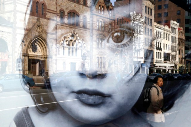 A woman pausing on Boylston Street is seen in the reflection of an advertisement on a bus stop in Boston, MA  March 13, 2016.