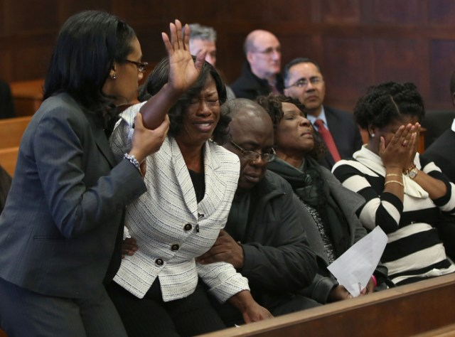 Germaine Vincent is helped back to her seat after her victim impact statement was read, in a Suffolk Superior courtroom, in Boston, MA, by her sister, Andrea Volcy, second from right.  She is flanked by former victim's advocate Majorie Tynes, left, and her husband, Julce Vincent, on January 27, 2016.  Her son's girlfriend, Vayola Vilma, covers her face, right.  Shabazz Augustine changes his plea to guilty in the 2004 killing of Vincent's 26-year-old daughter Julaine Jules, his former girlfriend.  He admitted to asphyxiating her, wrapping her body in plastic, weighing it down with free weights and throwing her into the Charles River in Cambridge.