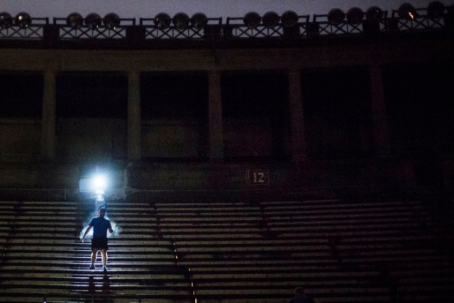 Nov. 30, 2016 — A member of the 5:30 a.m. section of the free exercise group The November Project is illuminated by a fellow runner's headlamp as he scales the stone steps of Harvard Stadium.