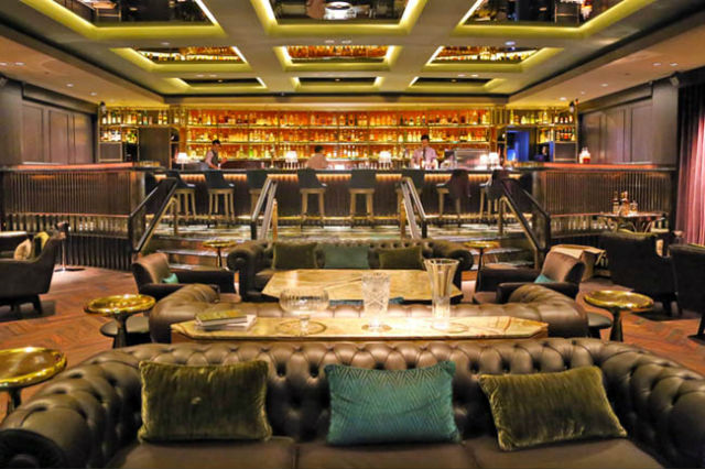 contemporary living room with black leather sofa chairs for inspiration: glamorous manhattan bar in regent - singapore