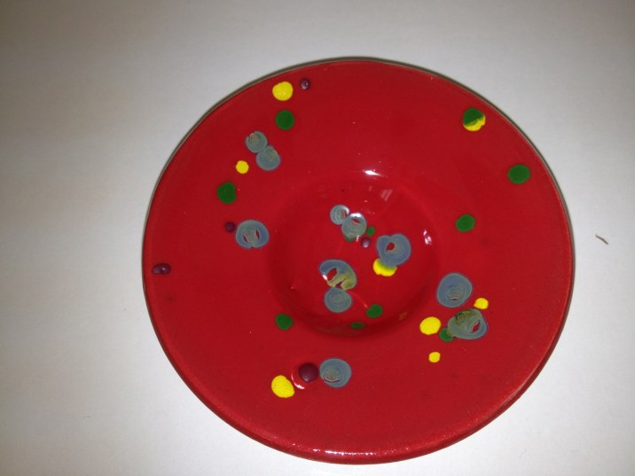 yellow, green, reactive blue crystals on low-fire red glaze