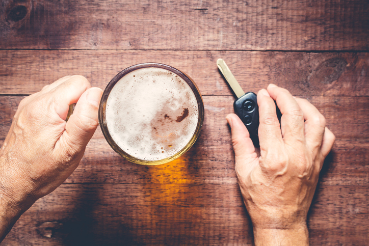Man hand drinking beer and holding car keys