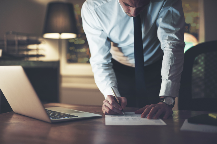 Serious businessman signing contract at office, working at night overtime