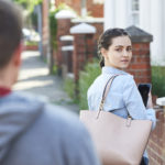 Young Woman Texting For Help On Mobile Phone Whilst Being Stalked On City Street