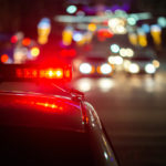 police car lights at night in city with selective focus and bokeh background blur