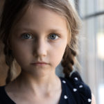 Crop close up portrait of serious sad little Caucasian girl look at camera, unhappy small child kid orphan feel lonely abandoned, outcast or loner miss parents, children drama, volunteer concept