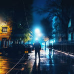 Silhouette of alone stranger in hood at night city street in rain. Creepy killer or stalker, criminal stands in shadow with urban lights reflected in puddles. Thriller horror mysterious atmosphere