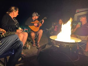 Jamie, Suzie and Paul enjoy Kyle playing the guitar around the campfire