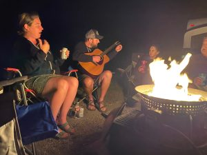 Jamie, Suzie and Paul enjoy Kyle playing the guitar around the campfire