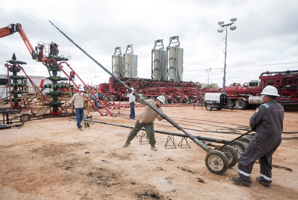 Arklatex Energy Services field hands set up the gun system while on location, Monday, Aug. 22, 2016, in Andrews, Texas.