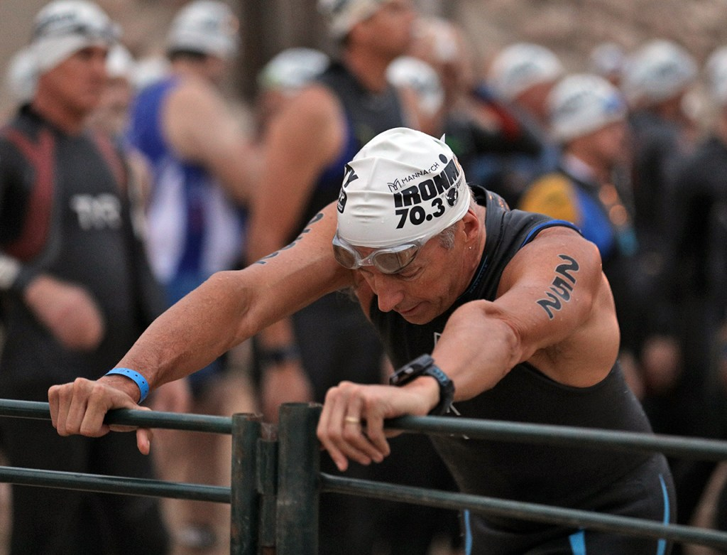 Kent Morris, from Conroe, stretches against against the fence before the swimming portion of the Ironman 70.3 Buffalo Springs Lake, Sunday, June 25, 2017, at Buffalo Springs Lake in Buffalo Springs, Texas. (Brad Tollefson/A-J Media)