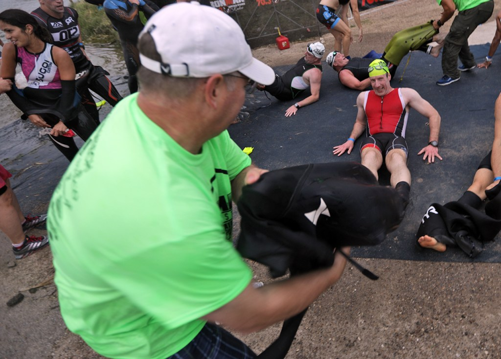 A volunteer helps pull the wet suit off a contestant during the Ironman 70.3 Buffalo Springs Lake, Sunday, June 25, 2017, at Buffalo Springs Lake in Buffalo Springs, Texas. (Brad Tollefson/A-J Media)