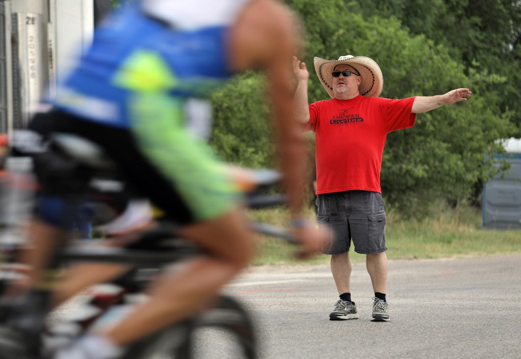 Mike Marsh, from Lubbock, tells cyclists where to turn during the Ironman 70.3 Buffalo Springs Lake, Sunday, June 25, 2017, at Buffalo Springs Lake in Buffalo Springs, Texas. (Brad Tollefson/A-J Media)