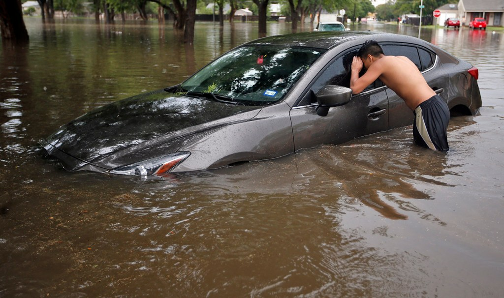 A Lubbock High student looks into his friends car to see the water level Wednesday, Aug. 31, 2016, near 23rd Street and Avenue W in Lubbock, Texas.