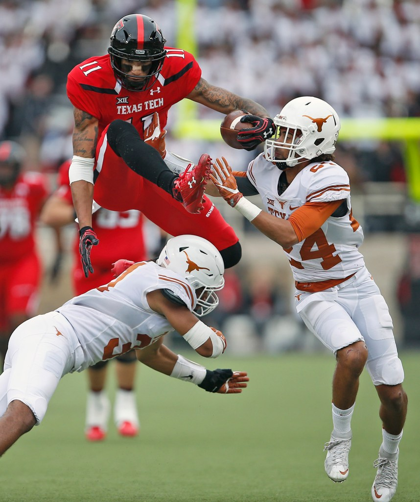 Texas Tech's Derrick Willies (11) jumps over Texas' Jason Hall (31) and around John Bonney (24) before fumbling the ball during an NCAA college football game Saturday, Nov. 5, 2016, in Lubbock, Texas.