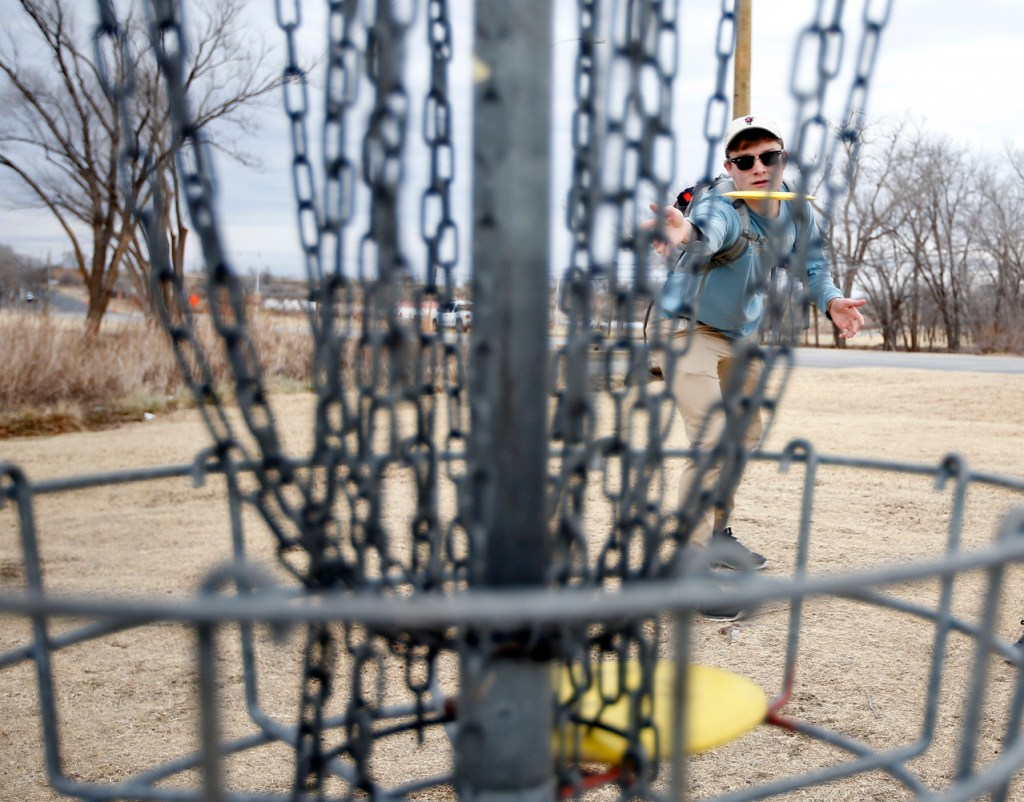 J.J. Logan, from Arlington, putts a disc toward the chains of the basket while playing disc golf with his friends Tuesday, Jan. 17, 2017, at Mackenzie Park in Lubbock, Texas. The friends went to the park to play a round while the weather was warm and before classes began at Texas Tech.