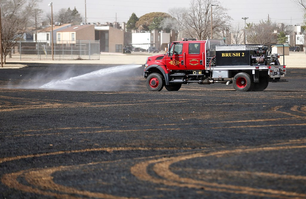 A firetruck sprays down a remaining hotspot from a grassfire Thursday, Feb. 23, 2017, at Dupree Park in Lubbock, Texas. The fire was called in at 12:23 and burned approximately 10 acres before it was contained.