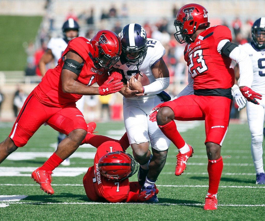 TCU's Shawn Robinson is tackled by Texas Tech's Jordyn Brooks