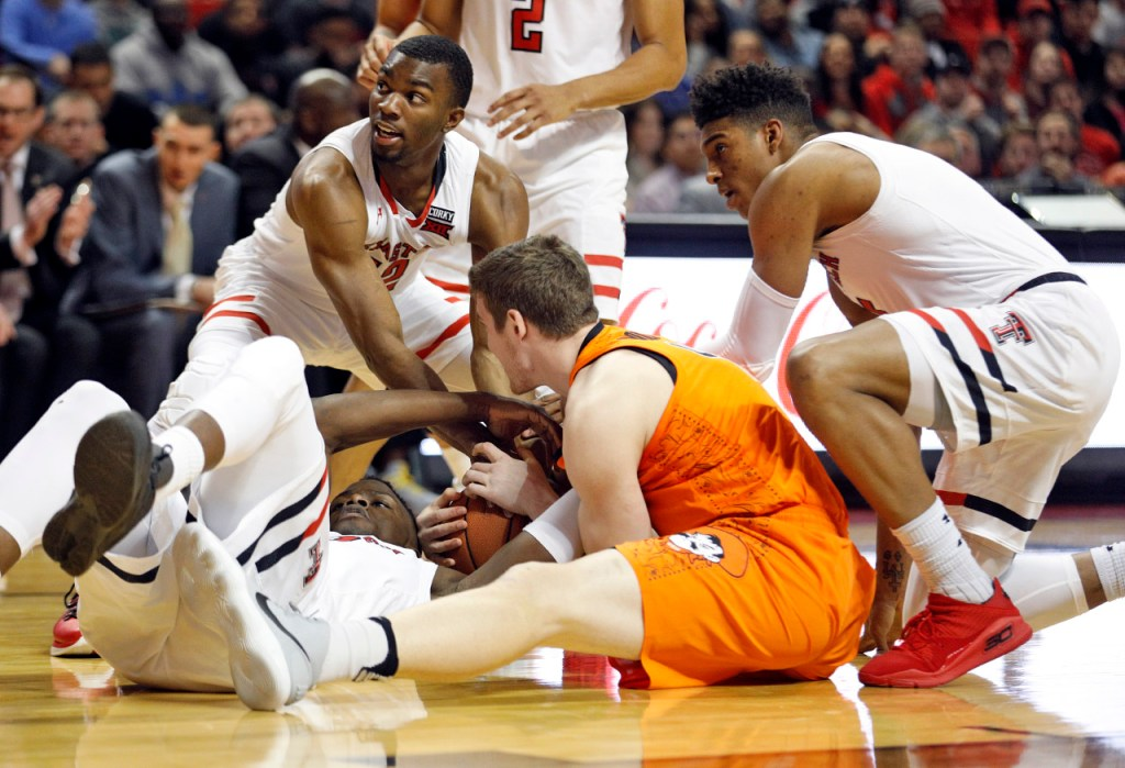 Oklahoma State's Mitchell Solomon (41) tries to keep the ball away from Texas Tech's Norense Odiase (32) and Keenan Evans (12) during the first half of an NCAA college basketball game Tuesday, Jan. 23, 2018, in Lubbock, Texas. (AP Photo/Brad Tollefson)