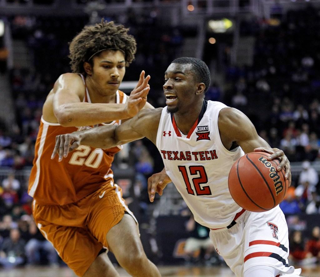 Texas Tech's Keenan Evans (12) drives the ball around Texas' Jericho Sims (20) during a Big 12 basketball tournament game Thursday, March 8, 2018, at the Sprint Center in Kansas City, Mo. [Brad Tollefson/A-J Media]