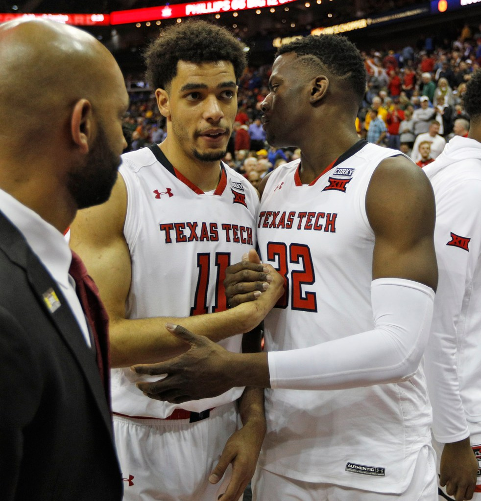 Texas Tech's Zach Smith (11) and Norense Odiase (32) hug after a Big 12 basketball tournament game against Texas, Thursday, March 8, 2018, at the Sprint Center in Kansas City, Mo. [Brad Tollefson/A-J Media]